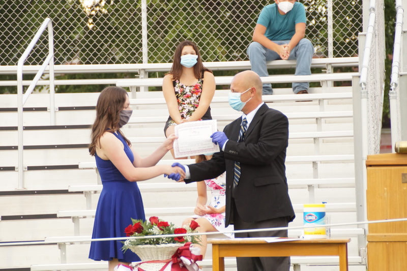 8th Grade Student receiving certificate of promotion from board president
